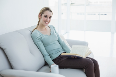 Cute blonde woman holding a book and a cup while sitting on couch smiling at camera photo