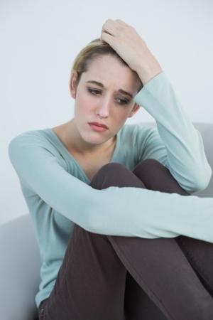 desolaci�n: Reflexiva mujer atractiva que se sienta en el sof� en la sala de estar