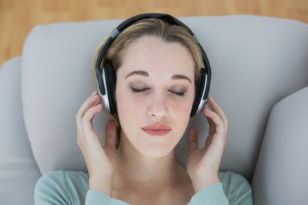 Pretty natural woman listening with headphones to music lying on couch with eyes closed photo