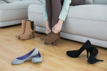Slim woman tying her shoelaces sitting on couch in living room photo
