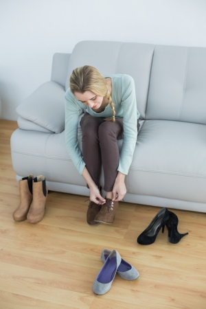 Attractive blonde woman tying her shoelaces sitting on couch in the living room photo