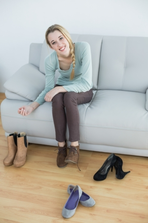 Gorgeous smiling woman tying her shoelaces sitting on couch looking at camera photo