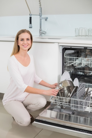 Lucky gorgeous model kneeling next to dish washer in bright kitchen photo