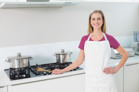 Casual happy blonde standing next to stove top  in bright kitchen