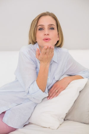 Happy casual blonde relaxing on couch blowing kiss in bright living room Stock Photo - 25433283