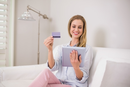 Smiling casual blonde using tablet for online shopping in bright living room photo