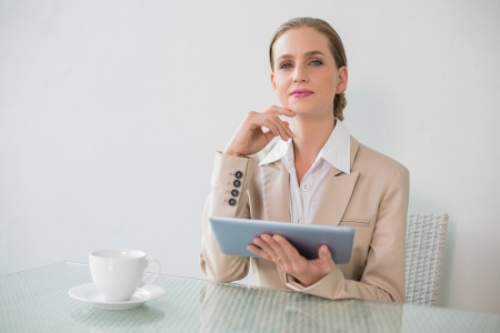 Content stylish businesswoman holding tablet in bright office photo