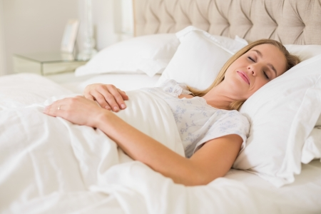 Natural calm woman slumbering in bed in bright bedroom photo