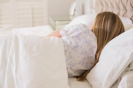 slumbering: Natural woman slumbering in bed in bright bedroom