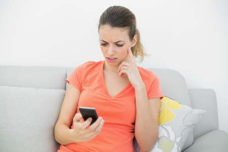 Troubled brunette woman using her smartphone sitting on couch in the living room