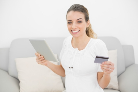 Attractive pregnant woman showing cheerfully her credit card and tablet smiling at camera photo