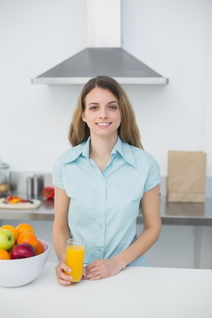 Content young woman posing in kitchen holding a glass of orange juice smiling at camera photo