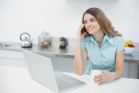 Pretty smiling woman sitting in her kitchen while holding a cup at home photo