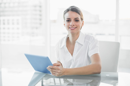 gleeful: Gleeful smiling businesswoman working with her tablet looking at camera sitting at her desk Stock Photo