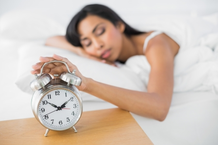 Attractive tired woman sleeping lying in her bed turning off the classic alarm clock photo