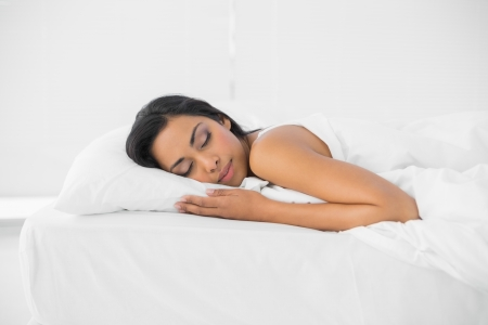 Calm sleeping woman lying on her bed in bright bedroom photo