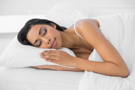 Beautiful sleeping woman lying under the cover on her bed in bright bedroom photo