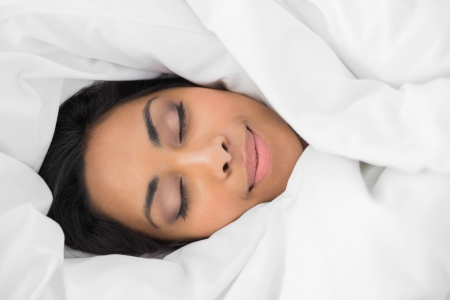 hair wrapped up: Lovely smiling woman lying on bed under cover with eyes closed