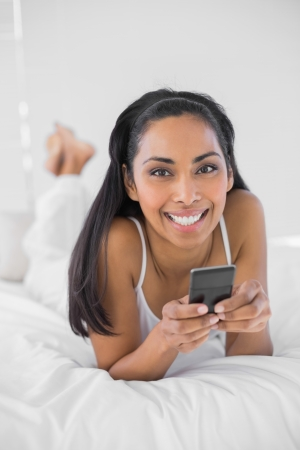 Beautiful smiling woman holding her smartphone smiling at camera lying on bed photo