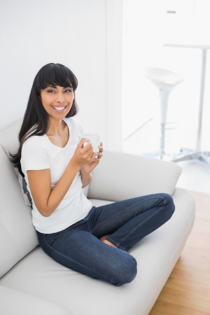 dark haired woman: Cheerful dark haired woman holding a cup sitting on couch smiling at camera
