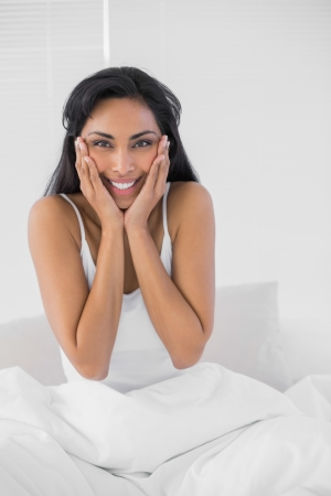 dark haired woman: Gleeful dark haired woman posing smiling at camera sitting on her bed Stock Photo