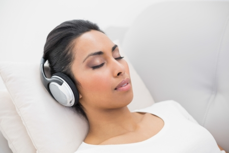 Lovely relaxing woman listening to music while lying on couch in bright living room