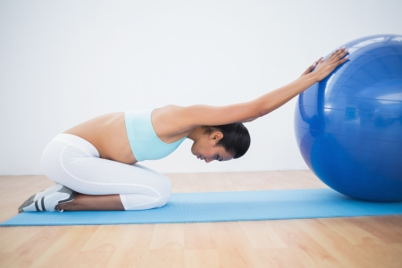 Lovely toned woman stretching her body with exercise ball on exercise mat