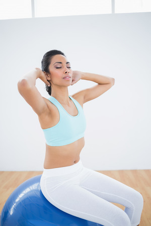 ball stretching: Calm sporty woman sitting on fitness ball stretching with eyes closed
