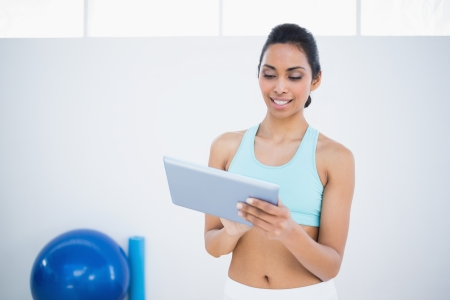 dark haired woman: Smiling dark haired woman using her tablet standing in fitness hall