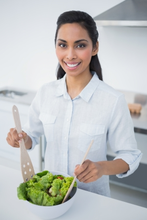 Attractive black haired woman preparing salad in kitchen smiling at camera photo