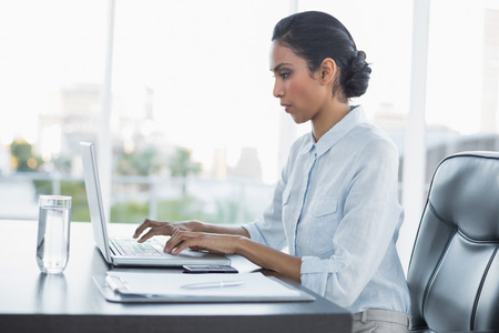 black hair: Young attentively working businesswoman sitting at her desk in the office