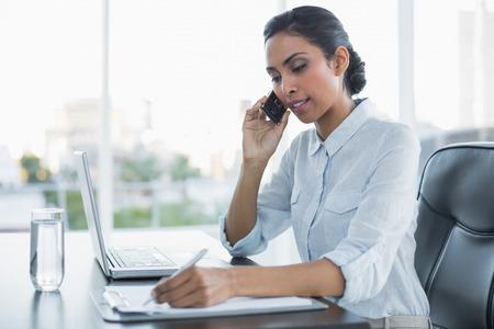 Arbeits sitzend Schöne Geschäftsfrau an ihrem Schreibtisch im Büro Lizenzfreie Bilder