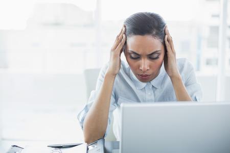 Pretty businesswoman suffering from headache sitting at her desk