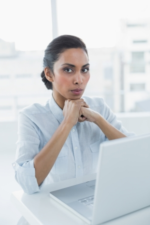 dark haired woman: Serious dark haired woman looking at camera sitting at her desk in bright office