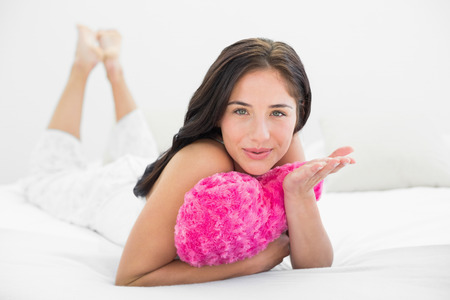Portrait of a young woman with heart shaped pillow blowing kiss in bed photo