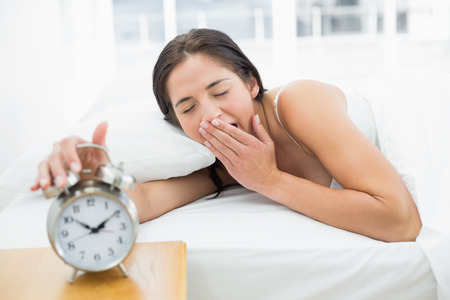 extending: Young woman yawning while extending hand to alarm clock in bed
