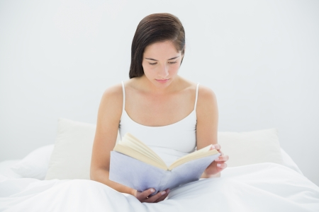 Young woman reading a book in bed at home photo