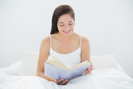 Smiling young woman reading a book in bed at home photo