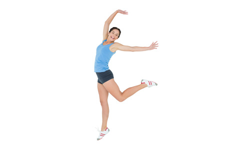 Full length of an active sporty young woman rejoicing over white background  Stock Photo - 25451378