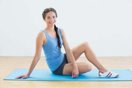 Full length portrait of a smiling young woman sitting on exercise mat photo