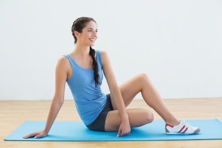 Full length of a smiling young woman sitting on exercise mat photo