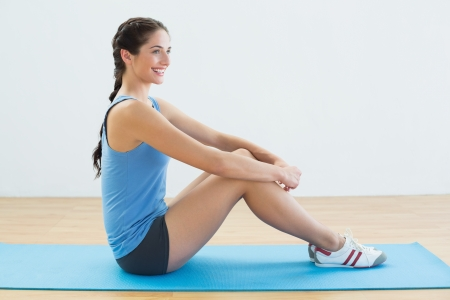 Full length profile shot of a fit young woman sitting upright on exercise mat photo