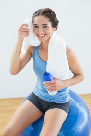 Portrait of a smiling young woman with towel around neck and waterbottle sitting on exercise ball photo