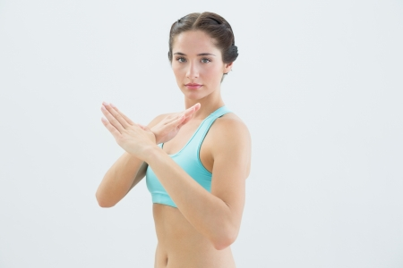 defensive posture: Portrait of a fit young woman standing in defending posture against white background Stock Photo