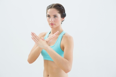 defensive posture: Fit young woman standing in defending posture against white background