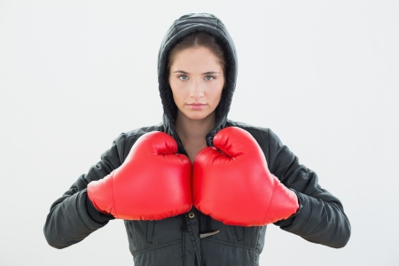 Portrait of a serious woman in red boxing gloves and black hood over white background photo