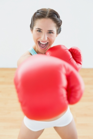 Close up portrait of a beautiful playful woman in red boxing gloves at fitness studio photo