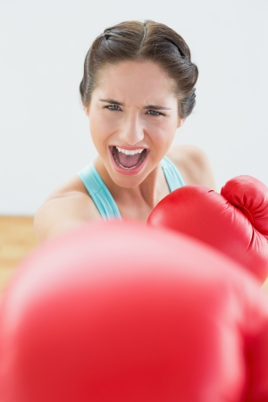 Close up portrait of a beautiful young woman in red boxing gloves at fitness studio photo