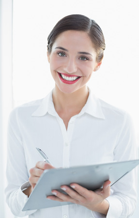 Portrait of a smiling young business woman with clipboard and pen over white background Stock Photo
