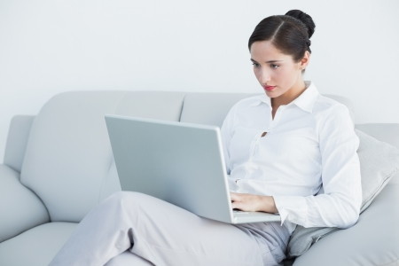 classy woman: Well dressed young woman using laptop on sofa at home Stock Photo
